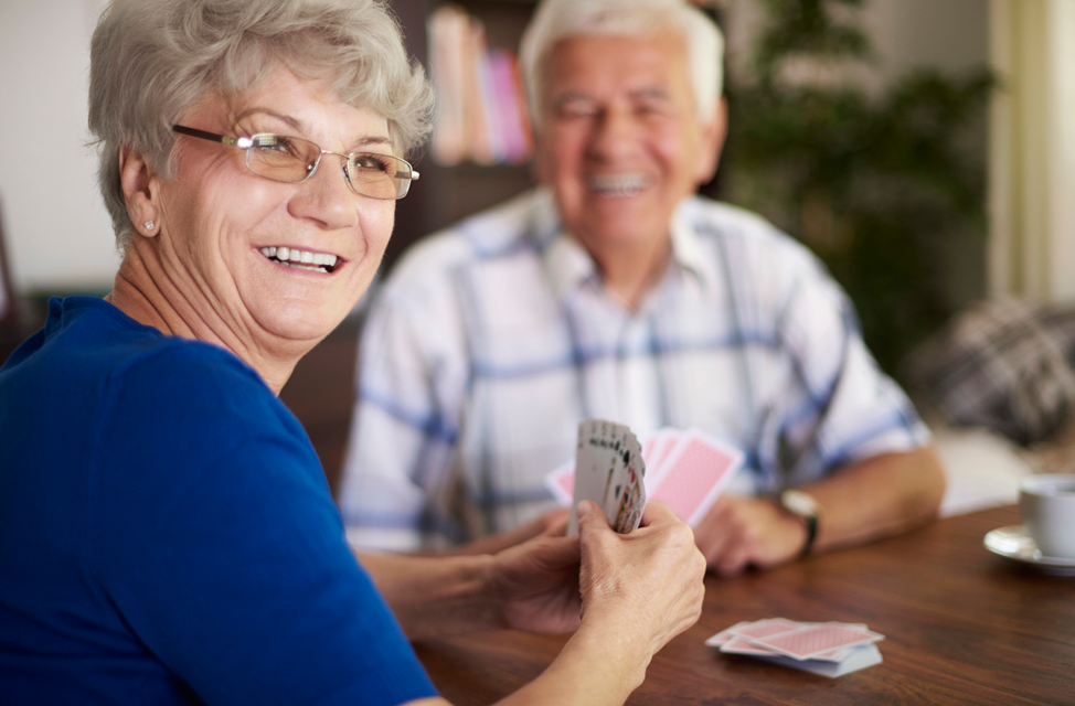 Senior Citizens are shown playing cards in the Community Room.
